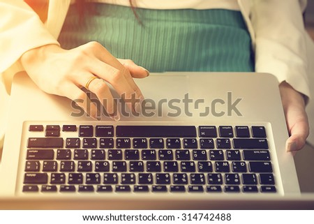 business woman working with laptop in office vintage tone. - stock photo