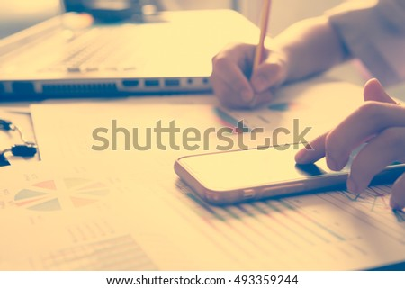 business woman working with laptop on wooden table with smart-phone