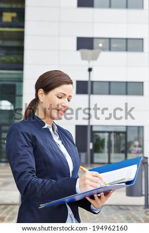 Business woman working with pen and files in front of her office in the city