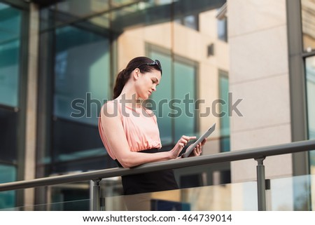 Business woman working with the tablet outdoors near the office
