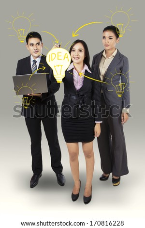 Business woman writing big idea with her business team
