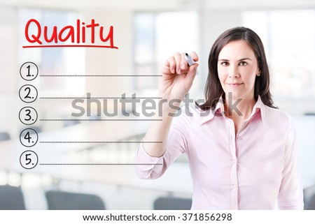 Business woman writing blank Quality list. Office background.  - stock photo