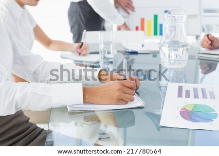 Business woman writing down notes at a meeting - stock photo