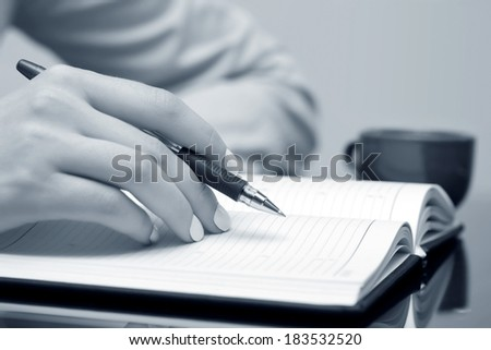 Business woman writing in notebook  - stock photo