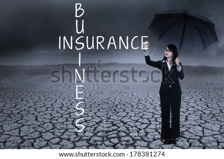 Business woman writing insurance concept on the air. shot outdoors - stock photo