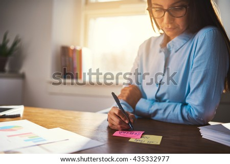 Business woman writing notes on post it in pink and yellow colours