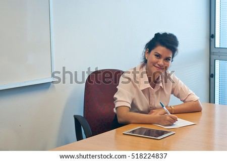 Business woman writing on a paper note