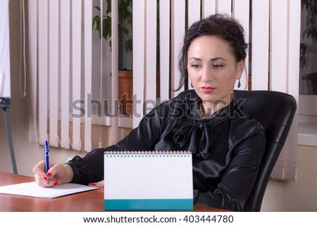 Business woman writing on a paper with a pensive look. Photo can be used as a whole background.