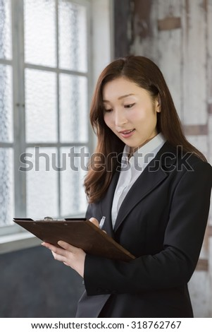 Business woman writing on clip-board