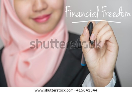 Business woman writing text : Financial Freedom over gray background - stock photo