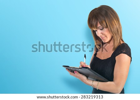 Business woman writting a document over colorful background