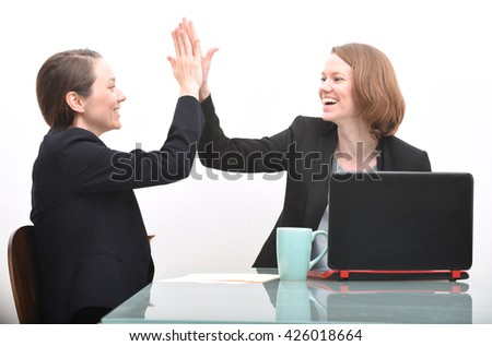 Business women and high five while celebrating a business accomplishment - stock photo