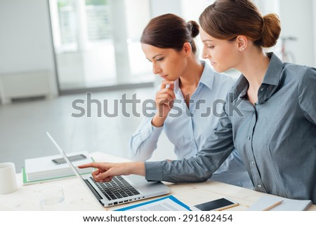 Business women at office desk working together on a laptop, teamwork concept - stock photo
