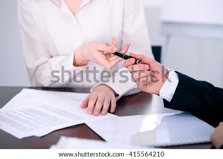 Business women giving a pen to business man for contract signing - stock photo