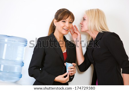 Business: Women Gossiping Around Water Cooler - stock photo
