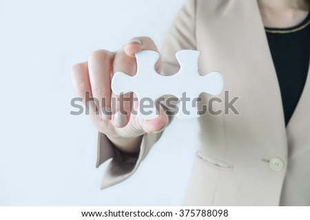 Business women holding a piece of jigsaw puzzle as business success concept - stock photo