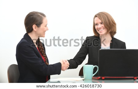 Business women in a job interview or business meeting shaking hands - stock photo