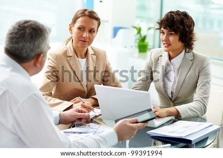 Business women listening attentively to their elder experienced colleague - stock photo