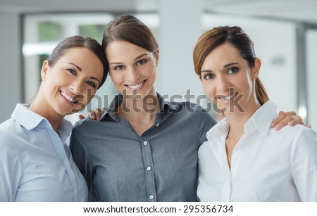Business women posing together in the office and smiling at camera, teamwork and women empowerment concept