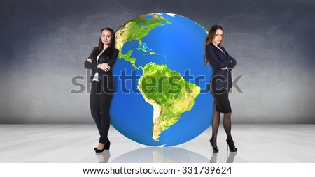 Business women stands near big earth ball in the gray room.Elements of this image furnished by NASA - stock photo