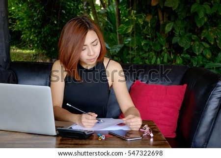 Business women working at cafe with laptop and documents on his desk