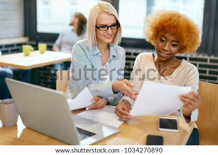 Business Women Working In Cafe. Beautiful Happy Young Female Co-workers Sitting At Table With Notebook And Working Together On Project. Teamwork. High Quality Image