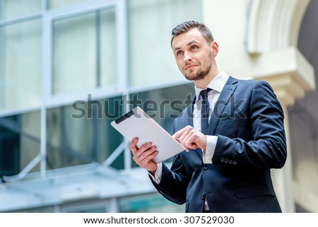 Business work on the tablet. Confident businessman looking to the side on the street and working on a tablet near the office building...... - stock photo