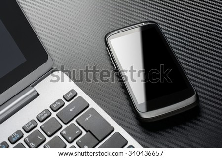 Business Work With Black Smartphone With Reflection Lying Right To A Notebook Keyboard, All Above A Carbon Layer