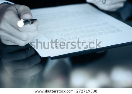 Business worker signing the contract to conclude a deal - stock photo
