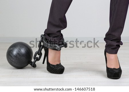 Business worker with ball and chain attached to foot - stock photo