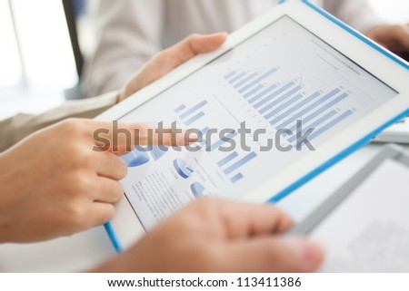 Business workers discussing digital graphs and diagrams indicating progress in work