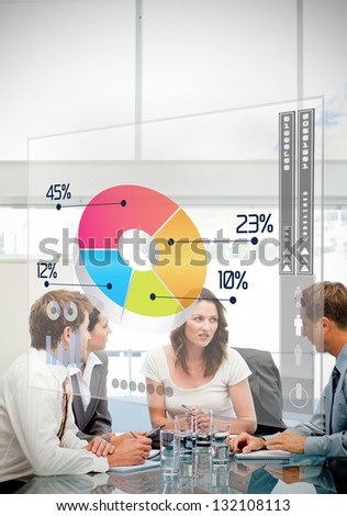 Business workers using colorful pie chart interface in a meeting