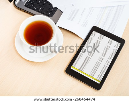 business workflow - above view cup of tea and tablet pc on office desk - stock photo