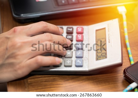 Business working concept. Female office using calculator at her office table. Vintage filter. - stock photo