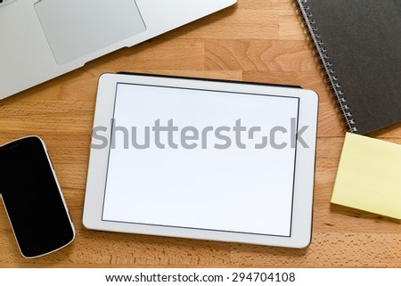Business working desk with tablet showing a blank screen for advertising - stock photo
