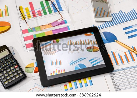 business workplace with digital tablet, mobile smartphone and some charts and graphs, pen - stock photo