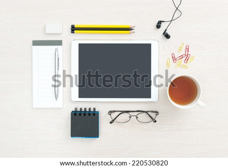 Business workplace with modern blank digital tablet, office supplies and objects for daily routine, regular items on a desk background. Top view. - stock photo