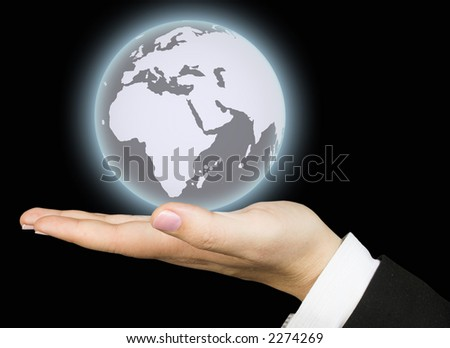 business world held by a hand over a black background - the business globe is glowing - stock photo
