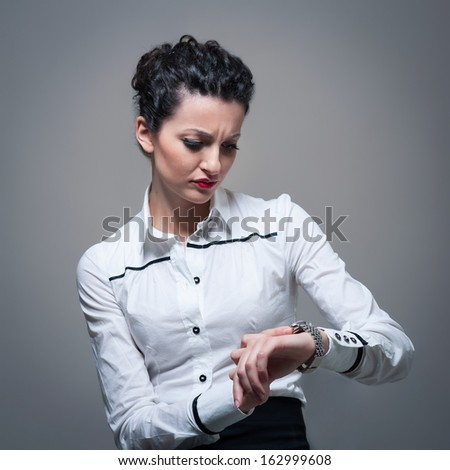Business worried woman looking at the time on her wrist watch.  - stock photo