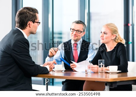 Business - young man in an Job interview, signs his employment contract with boss and his female assistant in their office - stock photo