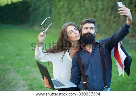 Business young pair of slim woman and man with long lush black beard with office devices of laptop glasses mobile phone paper folder and making photo standing outdoor on green grass, horizontal - stock photo