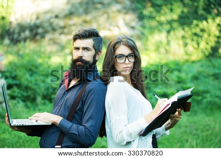 Business young pair of slim woman and man with long lush black beard with office devices of laptop glasses mobile phone paper folder and standing outdoor on green grass, horizontal photo - stock photo