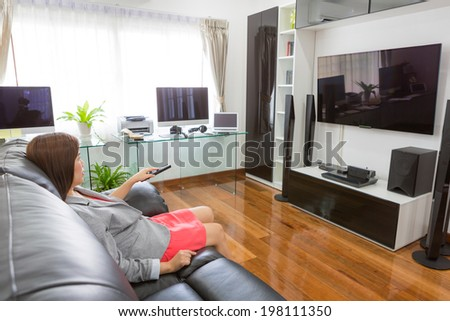 Business young woman watching TV in modern home office with computer and laptop - stock photo
