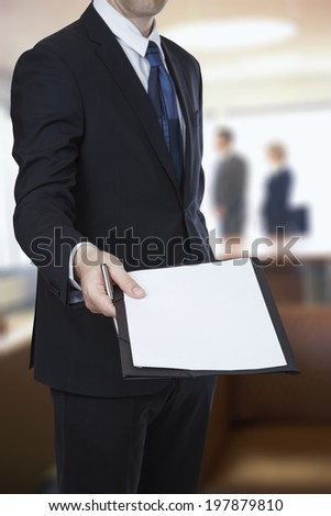 Businessman about handing an agreement paper on office background - stock photo