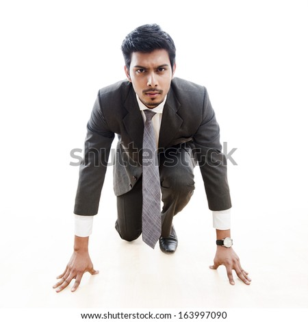 Businessman about to begin a race - stock photo