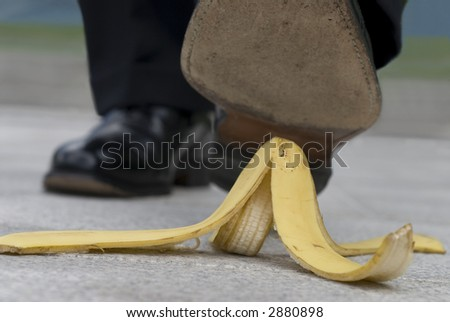 Businessman about to have an accident by stepping on a banana skin or peel. - stock photo