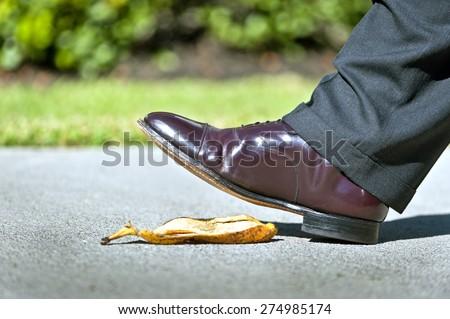 Businessman About To Slip On Banana Peel  - stock photo
