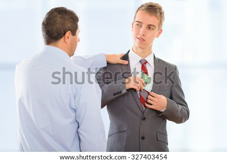 Businessman accepting bribe money and putting it in his pocket with a smile, while another businessman taps him on the shoulder. - stock photo