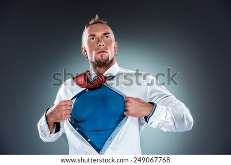 businessman acting like a super hero and tearing his shirt off on a gray background - stock photo