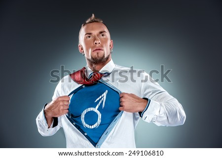 businessman, acting like a super hero or superman and tearing his shirt off on a gray background. Concept of decisive masculinity - stock photo